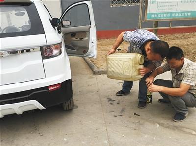 上图代步车生产公司,两名工人正在给一辆将要装车发货的燃油车加油