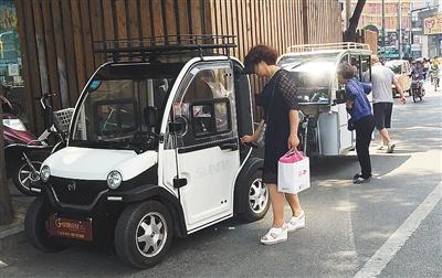 """5月18日,崇文门新世界商场附近,一名女士正拿钥匙去开""""老年代步车"""""""