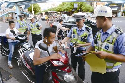昨天下午,交警在市区城开天桥下管理电动车。蒋文广 摄