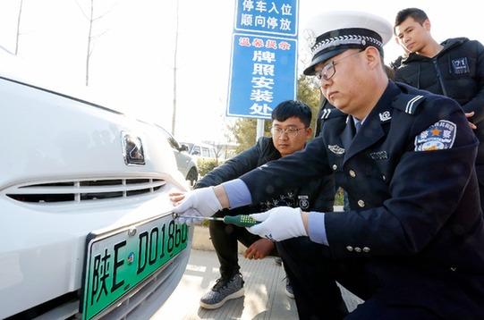 陕西民警正向消费者发放新能源汽车专用号牌