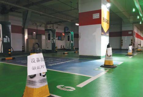 ▲国瑞城购物中心地下停车场充电车位处放有设备故障提示标。 图片来源:新京报