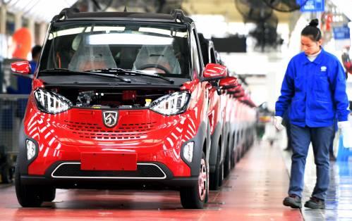 图为一名员工对准备下线的新能源汽车进行检测